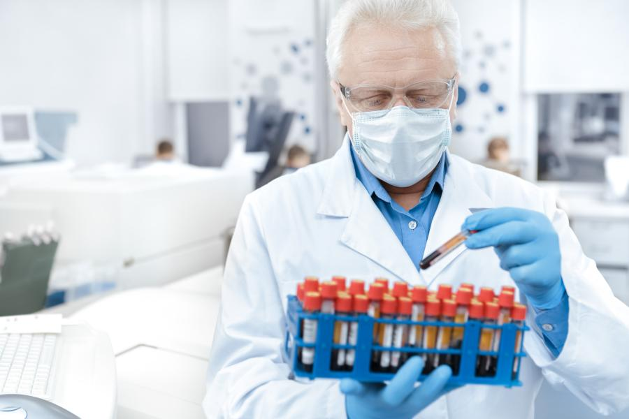 Scientist wearing protective mask working with blood samples in a laboratory