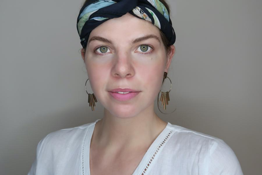 Young woman with headscarf looks into camera