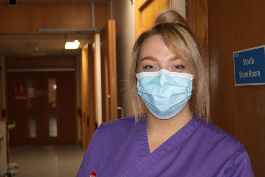 A student nurse wearing  purple uniform and a mask looks into the camera