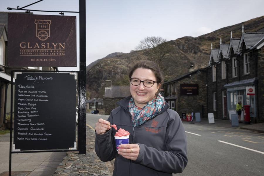 Young woman eats ice cream outside Glaslyn Ices, Bbeddgelert